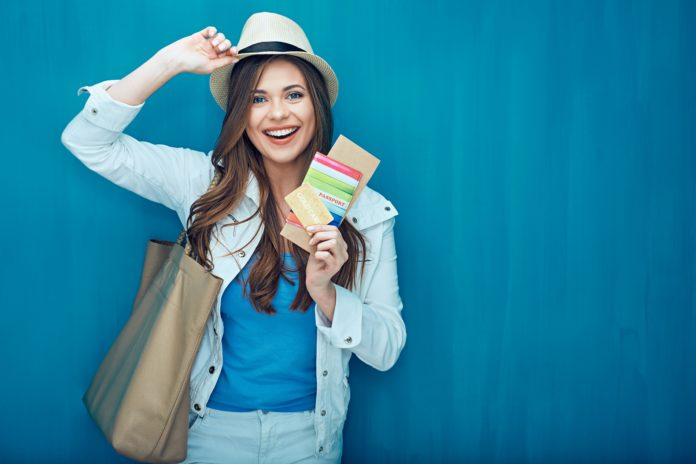 Smiling woman traveler holding passport with ticket.