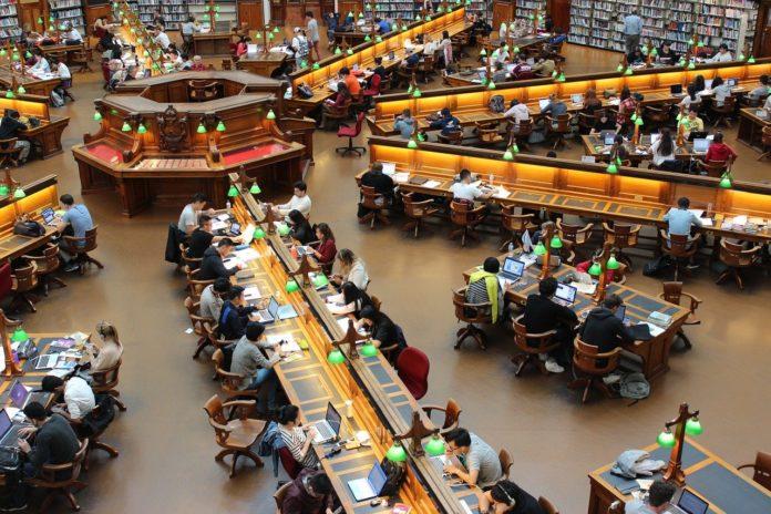 Eine große Bibliothek, in der zahlreiche Menschen an Schreibtischen arbeiten