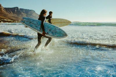 Surfer rennen ins Wasser