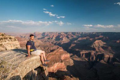 Ein junger Mann sitzt am Rande eines Felsens des Grand Canyons.